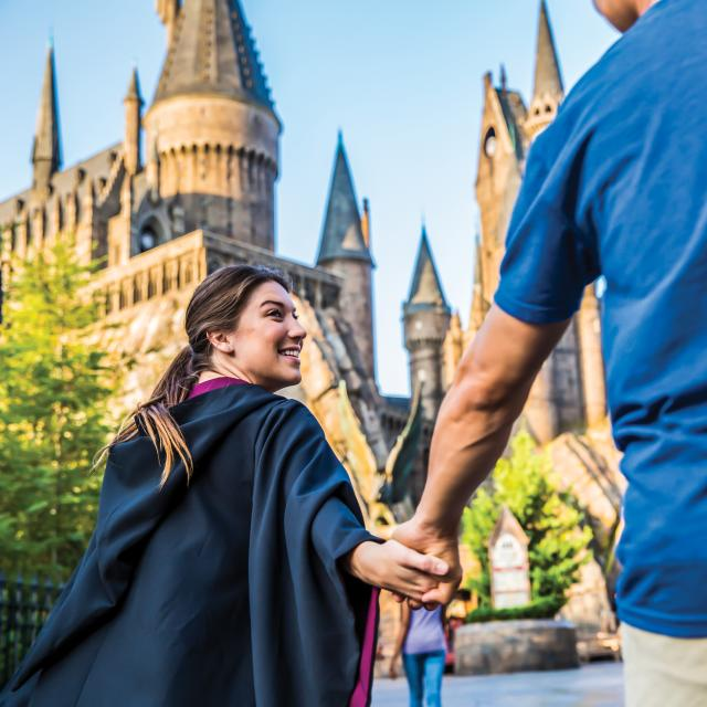 Couple at the Wizarding World of Harry Potter Hogsmeade at Universal's Islands of Adventure with Hogswarts Castle in the background