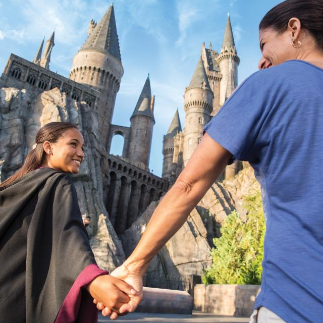 Mother and daughter at the Wizarding World of Harry Potter Hogsmeade at Universal's Islands of Adventure with Hogswarts Castle in the background