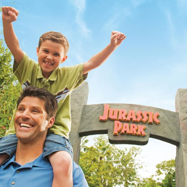 Universal's Islands of Adventure father and son posing in front of the Jurassic Park sign