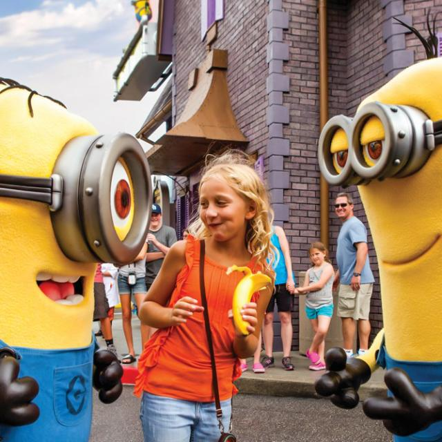 A girl holding a banana poses with two Minions at Universal Studios Florida