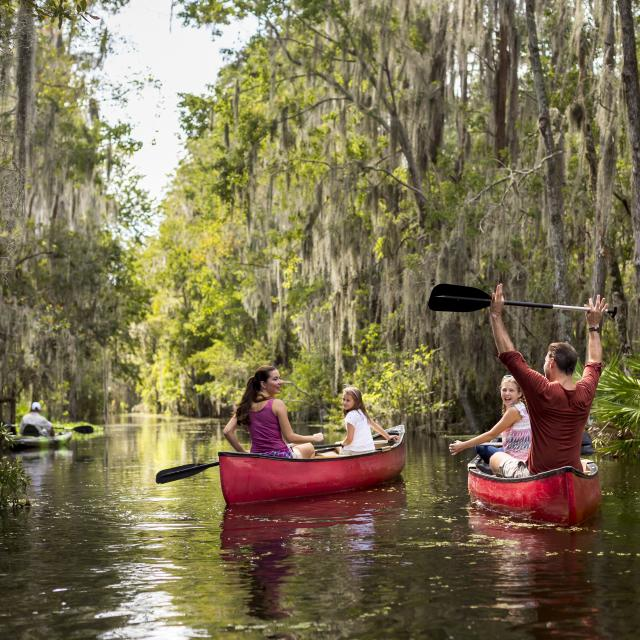 A family on canoes accompanied by a guide at JW Marriott Orlando, Grande Lakes.