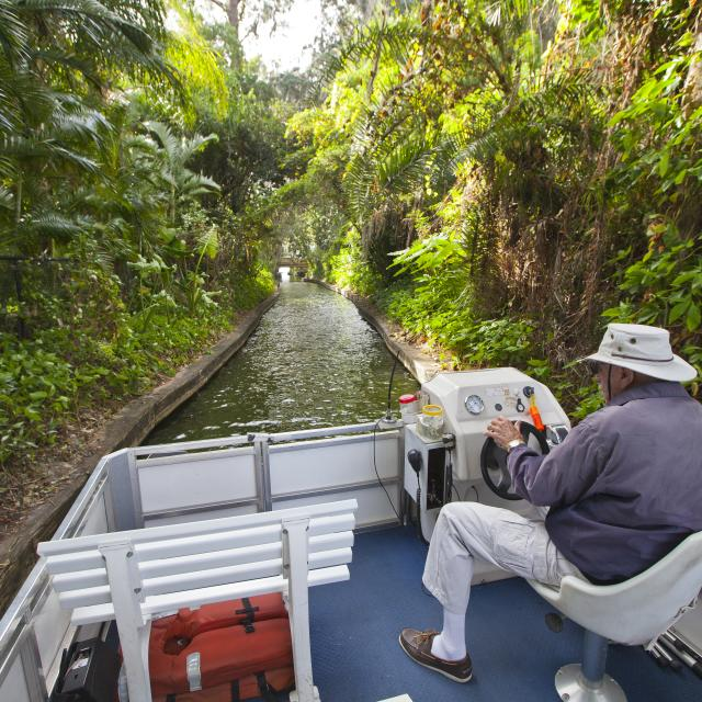 the captain steers the boat through a canal on the Winter Park Scenic Boat Tour