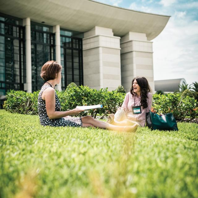Two women sitting in the grass outside of the Orlando/Orange County Convention Center West Building