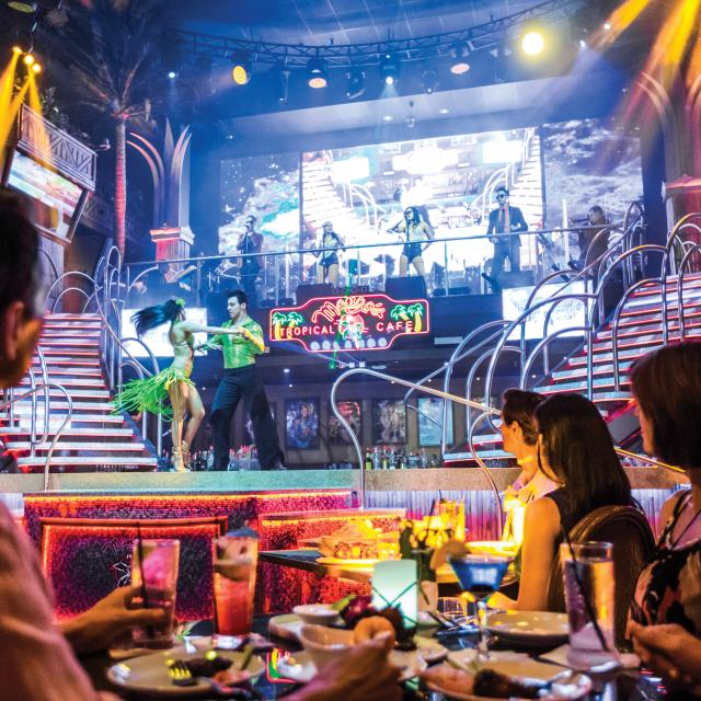 A group dining and watching a performance at Mango's Tropical Cafe Orlando