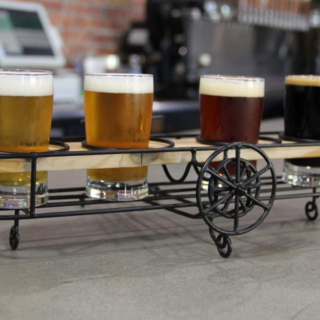 A flight of beer samples displayed apropros in wire-framed bi-plane-shaped holder at Crooked Can Brewing.