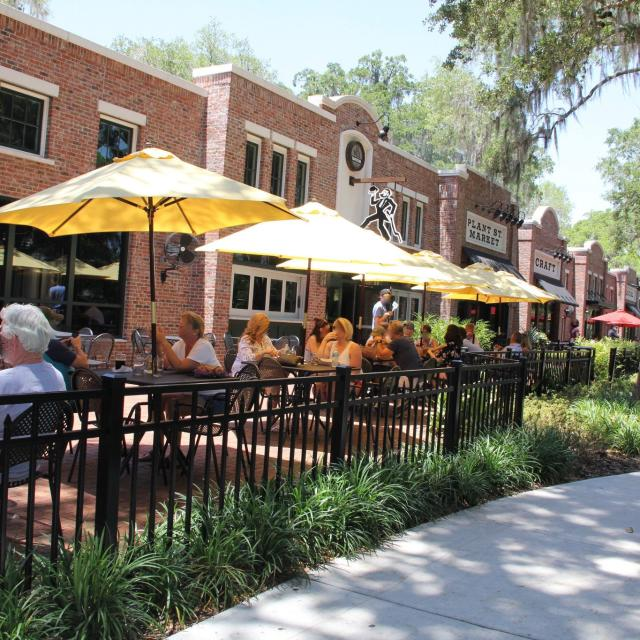 People sitting and drinking under umbrellas in outdoor dining area of Crooked Can Brewing Company at Plant Street Market in Winter Garden.
