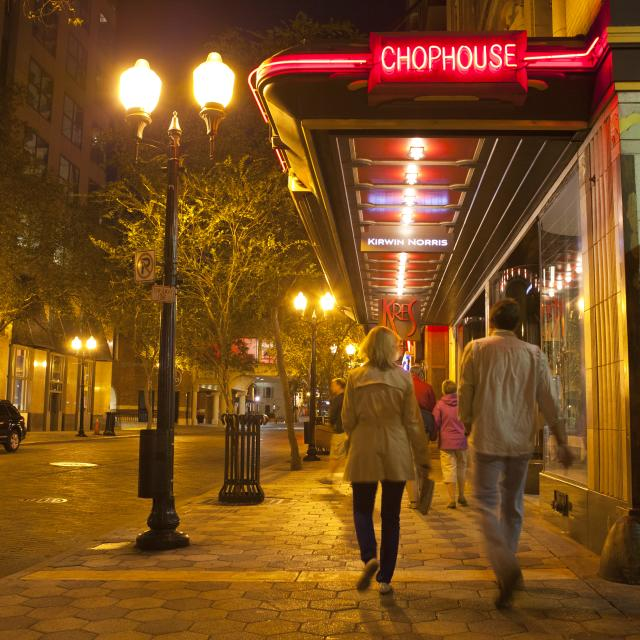 people walking by Kres restaurant at Church Street Station in downtown Orlando at night