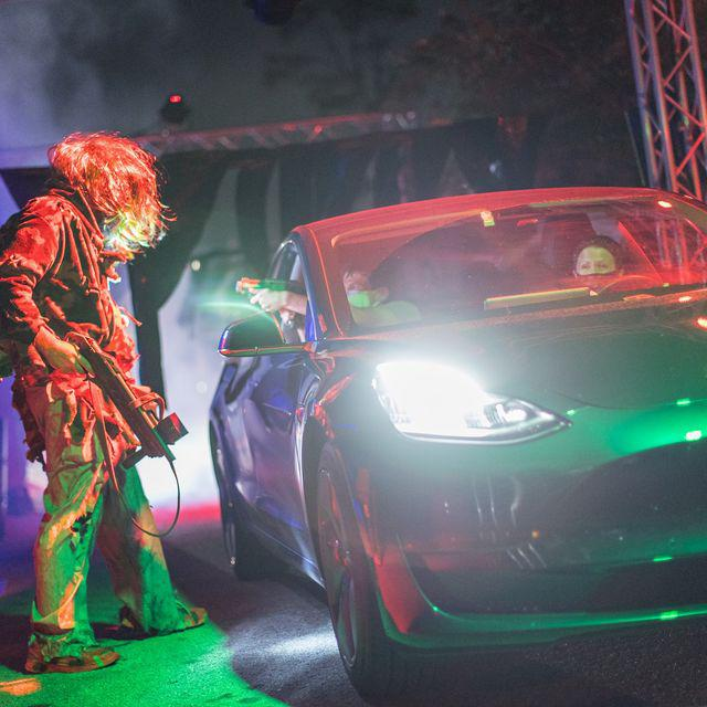 A zombie approaches a vehicle as it drives through Scream 'n' Stream, a Halloween attraction in Orlando.