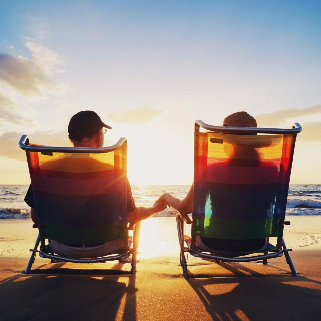 A senior couple sitting on the beach holding hands and watching the sunset