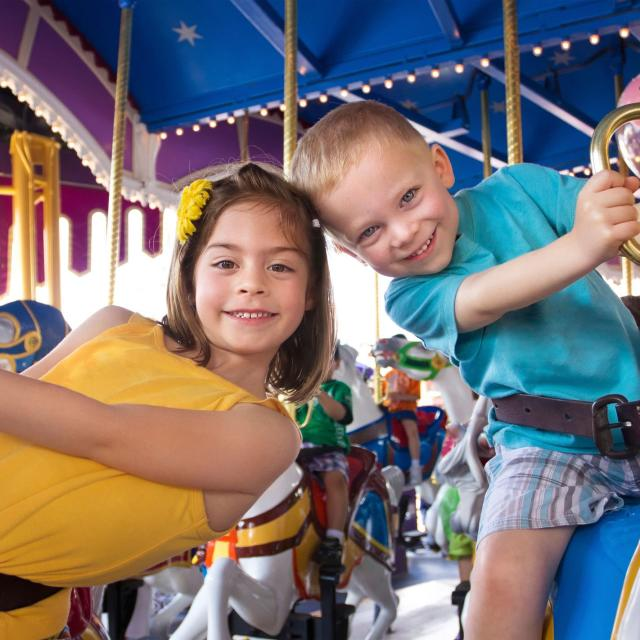 two children riding on a carousel