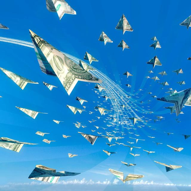 Paper airplanes made of dollar bills flying in a blue sky