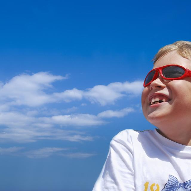 a young boy wearing sunglasses and smiling