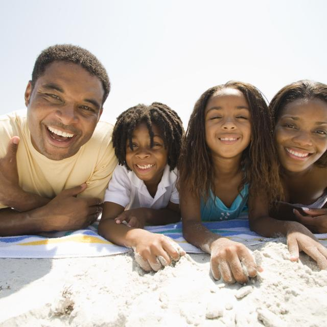 African-American family laying on a towel at the beach