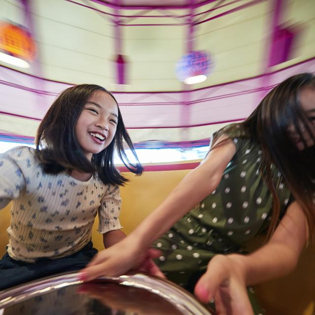 Sisters spinning on the Mad Tea Party ride at the Magic Kingdom in the Walt Disney World Resort