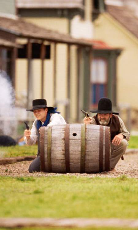 Two men hide behind a barrel in a reenactment at Boot Hill Museum