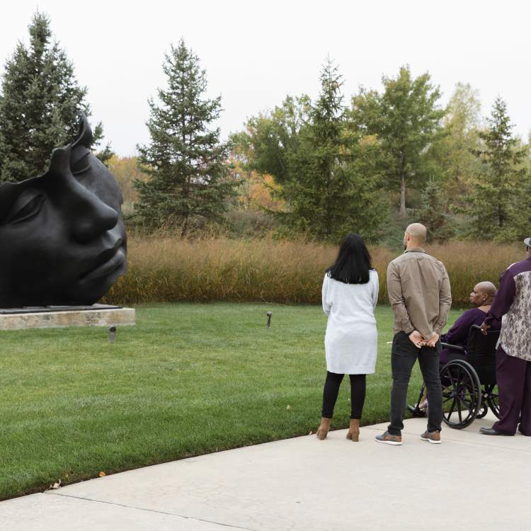 Visitors taking Igor Mitoraj's Light of the Moon - Further Out out Frederik Meijer Gardens & Scuplture Park.