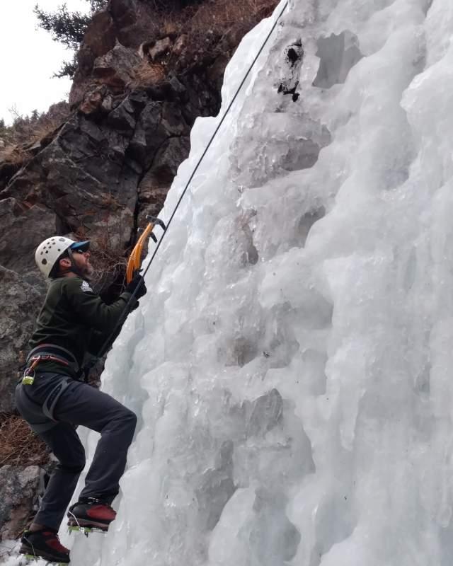 An American Alpine Club member climbs a frozen waterfall.