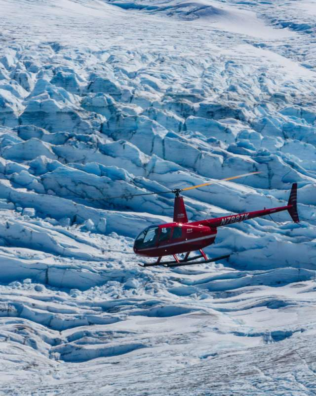 Helicopter flying above a glacier field