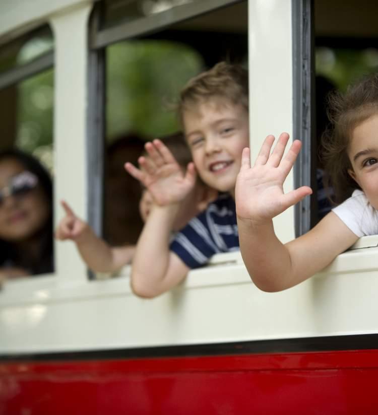 kids waving from the streetcar windows