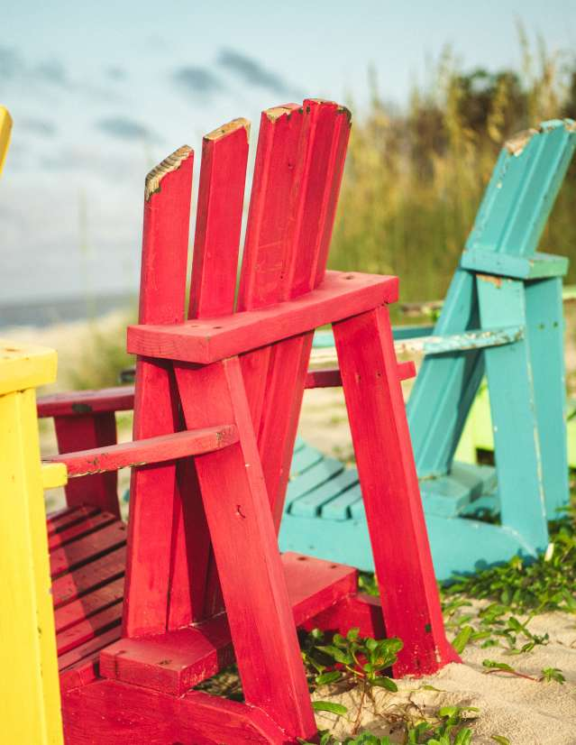 Four brightly colored Adirondack chairs on a beach with green vines.