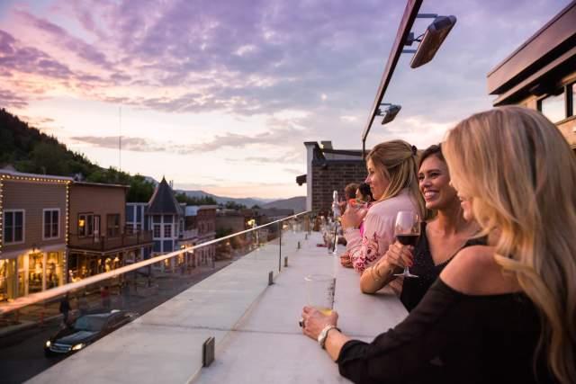Women enjoying cocktails at Spur Bar overlooking Historic Main Street