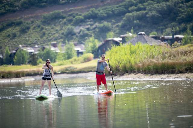Adults paddle boarding