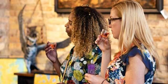 Two woman in an art gallery tasting wine