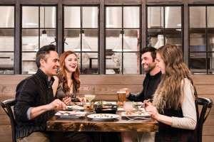 Four adults enjoying dinner at Firewood