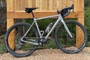 Grey gravel bike leaning against trail sign