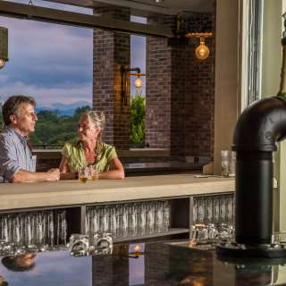 A couple enjoys the beautiful views from Green Man Brewing in Asheville, NC