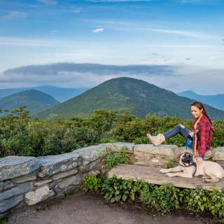 A young woman sits with her dog at Craggy Gardens Pinnacle near Asheville, NC