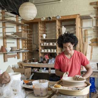 Ceramic artist Tristan Glosby works at the pottery wheel at Clayspace Co-op in the River Arts District of Asheville, North Carolina.