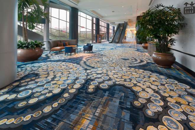 Photo of concourse in the downtown Houston Hilton hotel with large windows, daylight and swirling carpet pattern