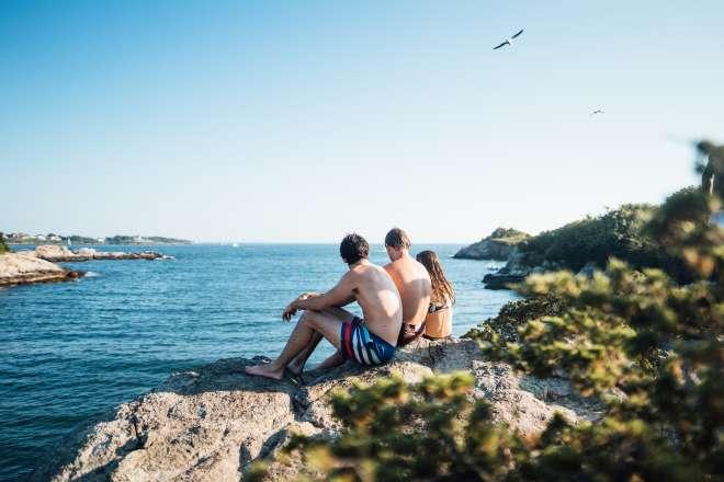 three people sitting on waters edge