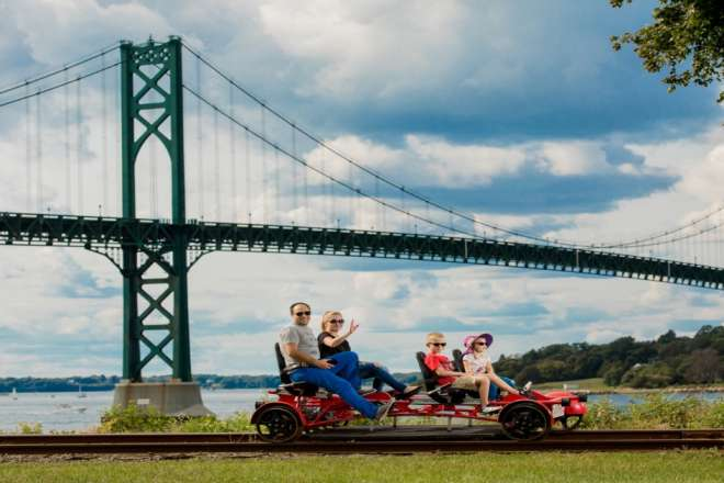 People riding rail bikes on a railroad bridge in Portsmouth RI