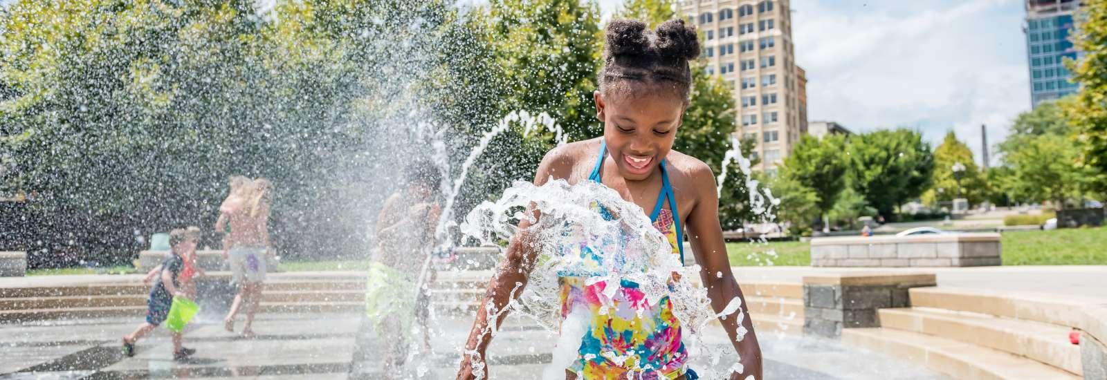 Girl playing in fountain at Splashveille park in Asheville
