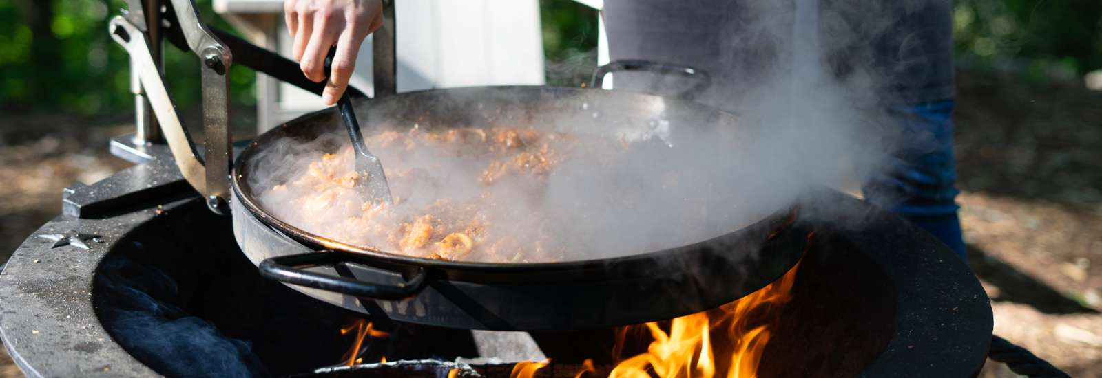 Paella cooking over a grill