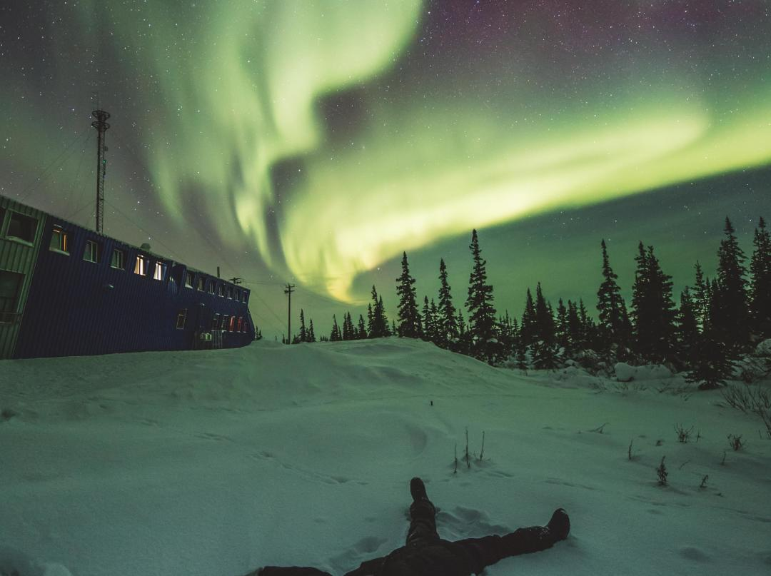 Making snow angels under the northern lights in Churchill, Manitoba