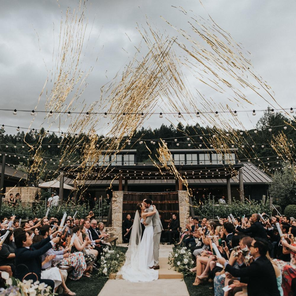 Bride and Groom kissing at the alter with guests shooting gold streamers in the air
