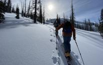 Two Backcountry skiers hiking up mountain on skis