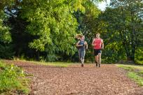 A couple runs on a bark mulch trail in a forested area.