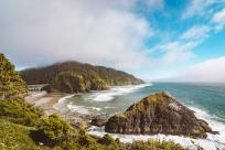 Viewpoint from Heceta Head Lighthouse showing rocky coastline and a large bridge.