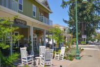 Friends sit in white rocking chairs in front of a wine bar on main street in charming, historic Coburg.