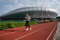 A woman running on a track surface in front of Hayward Field.