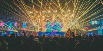 Lights and lasers over a crowd at an electronic music concert