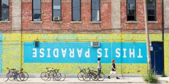 """People walk by a wall mural that reads """"This is Paradise"""" in Toronto's Queen Street West neighbourhood"""