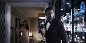 A man in a suit holding a wine glass with a woman in a long dress walks to him at the Fairmont Royal York hotel room in Toronto