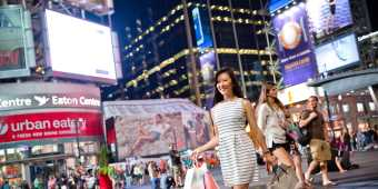 A woman walks with shopping bags outside the Eaton Centre shopping mall at night