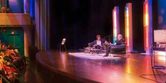 attendees watch presenters on a stage for the International Festival of Authors