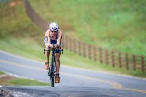 Chattanooga Ironman participants rides bike on road with field behind them.